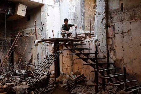 A Free Syrian Army fighter sits atop a flight of stairs near the Grand Umayyad mosque in Aleppo